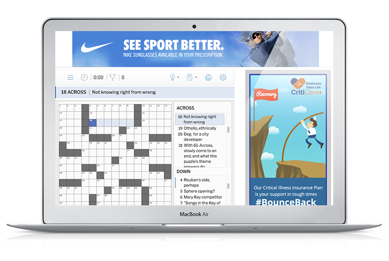 A MacBook Air showing a PuzzleMe crossword embedded on a page